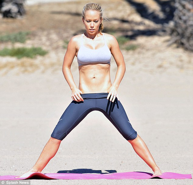 Killer abs: Kendra Wilkinson showed off her washboard abs and amazing physique as she worked out on the beach in Los Angeles on Thursday