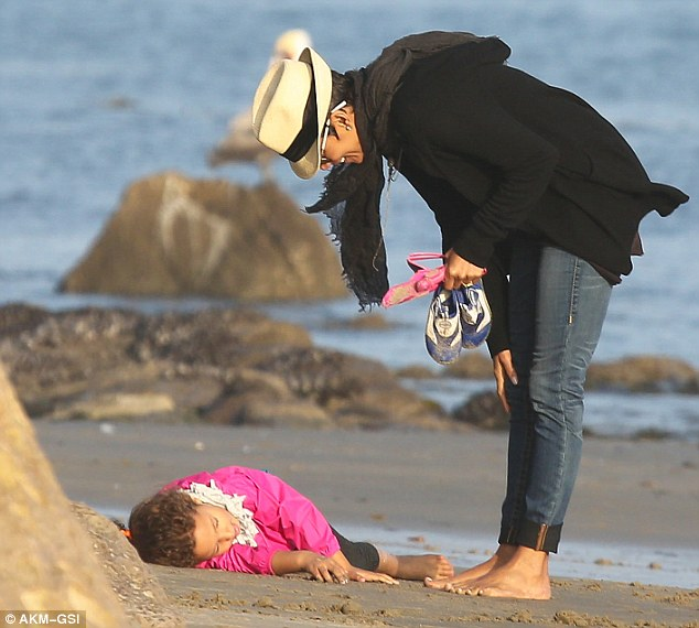 Tiring work: Nahla pretended to go to sleep during their walk as her smiling mother looked on