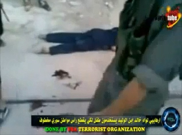 Disturbing: The beheaded man can be seen lying in the background while chants of Allahu Akbar', or 'God is great' can be heard