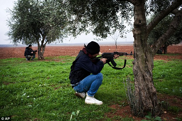 A pair of Free Syrian Army fighters aim their AK47s over a field as they prepare for the attack on the military base