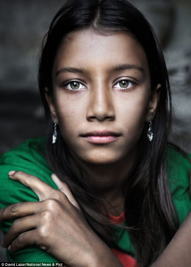 Beauty: The girl with the green eyes was spotted playing in a Bangladeshi village by a travel photographer