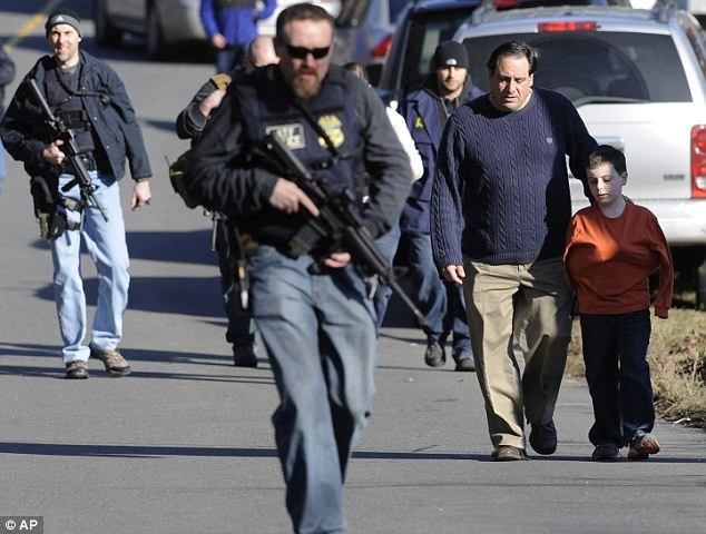 Parents leave a staging area after being reunited with their children following a shooting at the Sandy Hook Elementary School