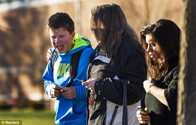 A boy weeps as he is told what happened after being picked up at Reed Intermediate School following the Sandy Hook Elementary School shooting