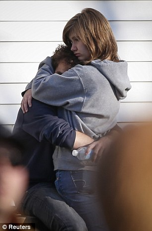 A couple embrace each other near Sandy Hook Elementary School, were a gunman opened fire on school children and staff in Newtown, Connecticut