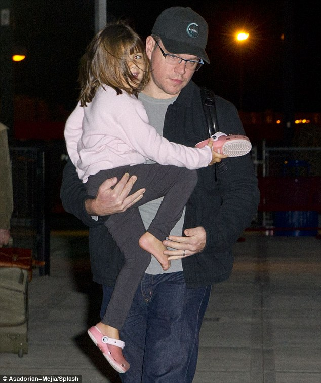 Action man: Matt Damon's muscles came in handy when he carried daughter Gia at the airport in New York on Friday