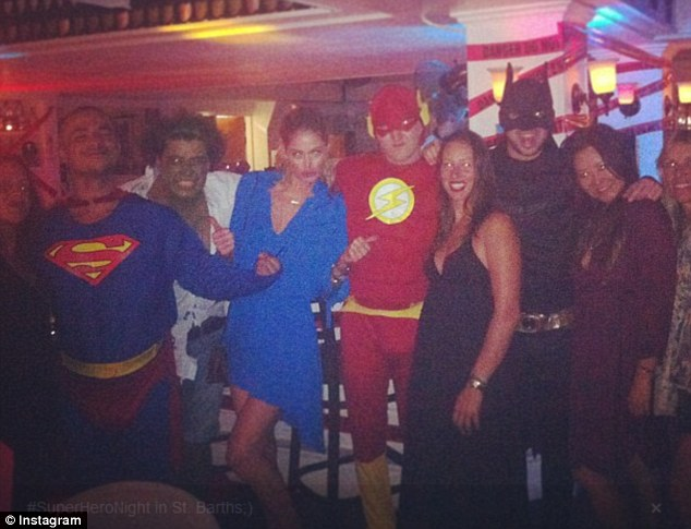 Super model: The model looked more like Super Woman as she posed with a few costumed friends at a bar in St. Barts