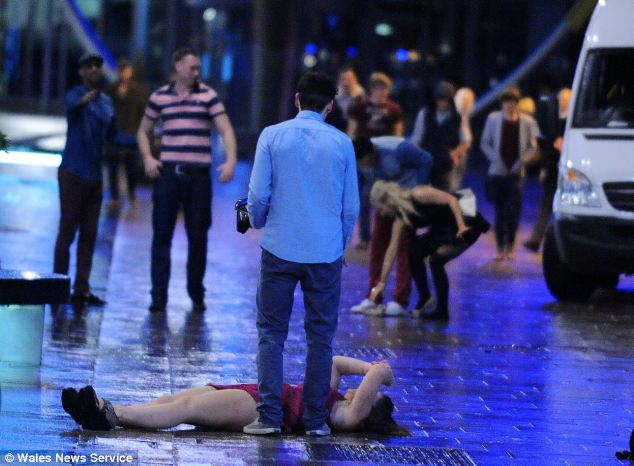 Out for the count: Woman lies drunk on soaking pavement and is oblivious to the cold and rain