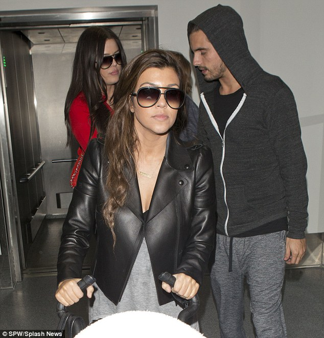 Yummy mummy: Kourtney looked stylish in a black cropped leather jacket but hid her eyes behind a large pair of shades