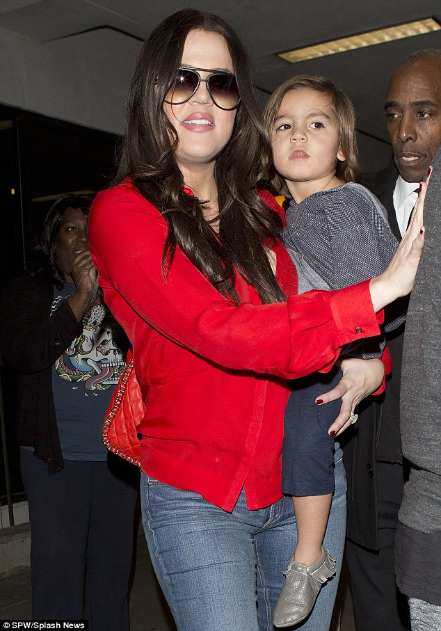 Take me home: Khloe was every inch the doting auntie as she carried tired Mason home following their flight back to LA