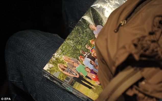 Remembering those not there: A woman brought a class photo that included some of the victims