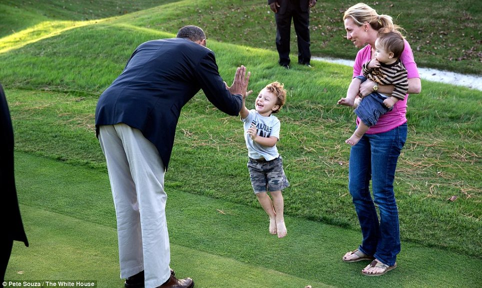 Obama high-fives an adorable kid on the links at Andrews Air Force Base during a golf outing