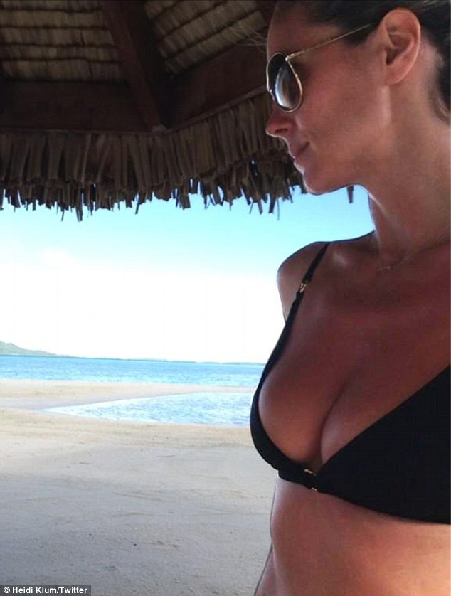 'Thank you for another beautiful day!': Heidi Klum tweeted this picture while holidaying at in a secret destination