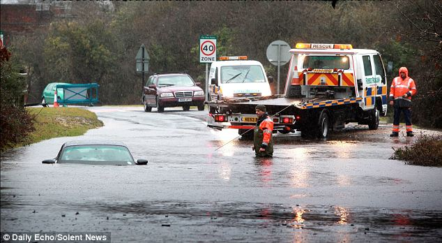 Water pity: The driver of this Porsche 911 and his daughter had a lucky escape when they climbed out of the windows - after the car was submerged by water