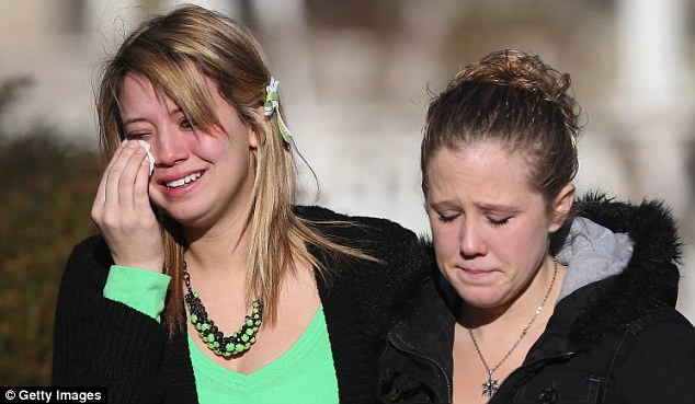 Grief: Mourners leave the funeral of six-year-old Jesse Lewis as the long line of funerals continued today in Newtown