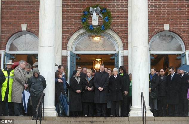 Silence: Governor Dannel Malloy listens to the ringing of a bell 26 times at Edmond Town Hall this morning