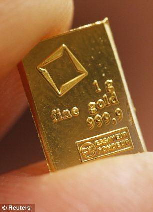 An employee shows a 1 gram piece of a gold Combibar