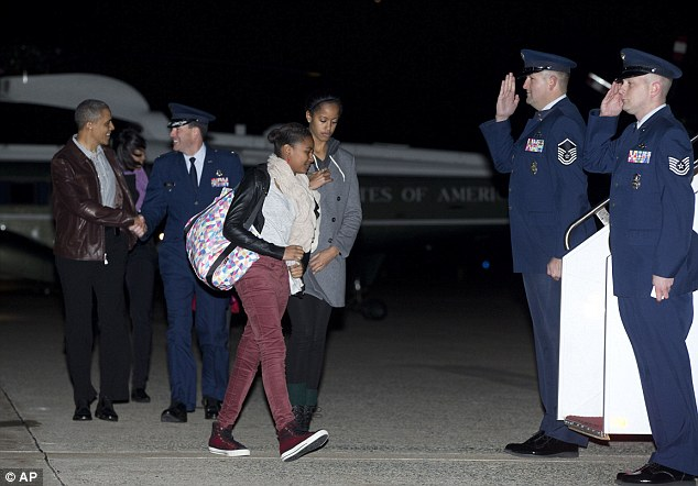 Salute: President Barack Obama, First Lady Michelle Obama and their daughters Malia and Sasha walk from Marine One to board Air Force One