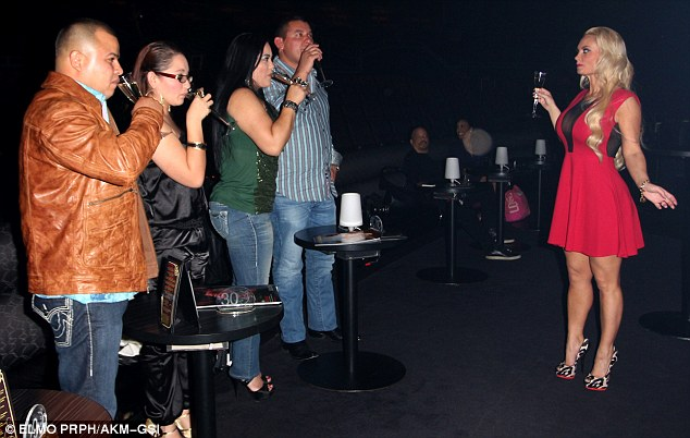 I'll drink to that! Coco toasts fans at the Planet Hollywood Hotel and Casino