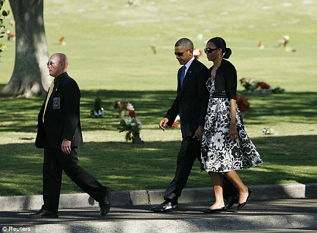 In mourning: President Obama and first lady Michelle Obama walk with Gene Castagnetti, Director of the National Memorial Cemetery of the Pacific, as they arrive for Senator Daniel Inouye's memorial ceremony in Honolulu