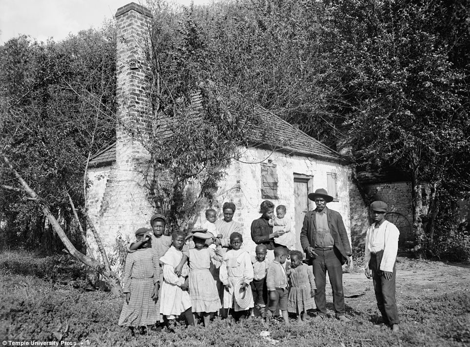 New life: A whole family poses by a building in Savannah, Georgia in 1907