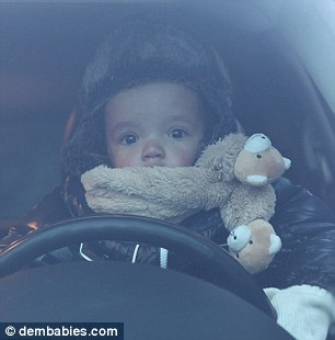 Those eyes! Moroccan looked super-cute with a green star decoration stuck on his forehead and in another shot his famous parents propped him up behind the driver's seat of a car
