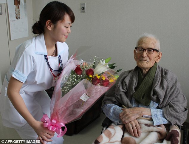 Celebration: Mr Kimura is handed a bouquet of flowers by a nurse as he is declared the record holder