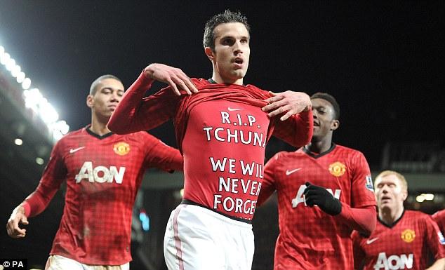For you: Van Persie is mobbed by his team-mates after scoring, but he manages to get his message across