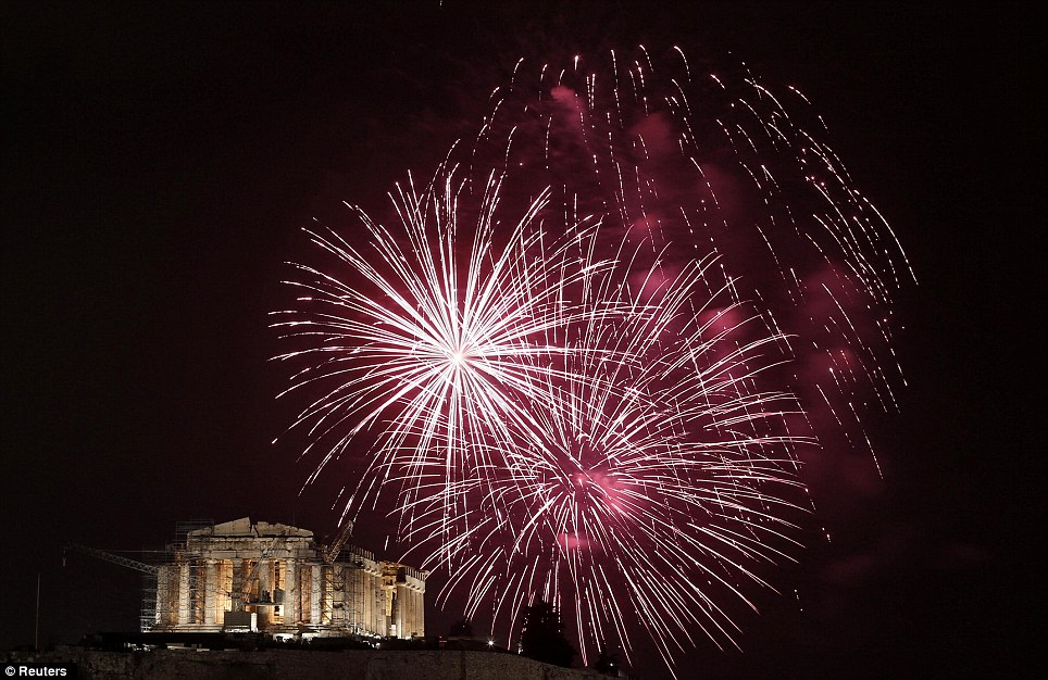 Muted: Fireworks explode over the temple of the Parthenon during New Year celebrations in Athens