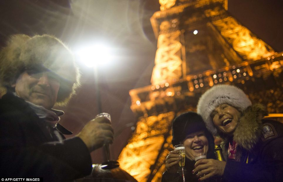 People toast with a bottle of Champagne as they celebrate the New Year on the Trocadero square beside the Eiffel Tower in Paris, early on January 1, 2013