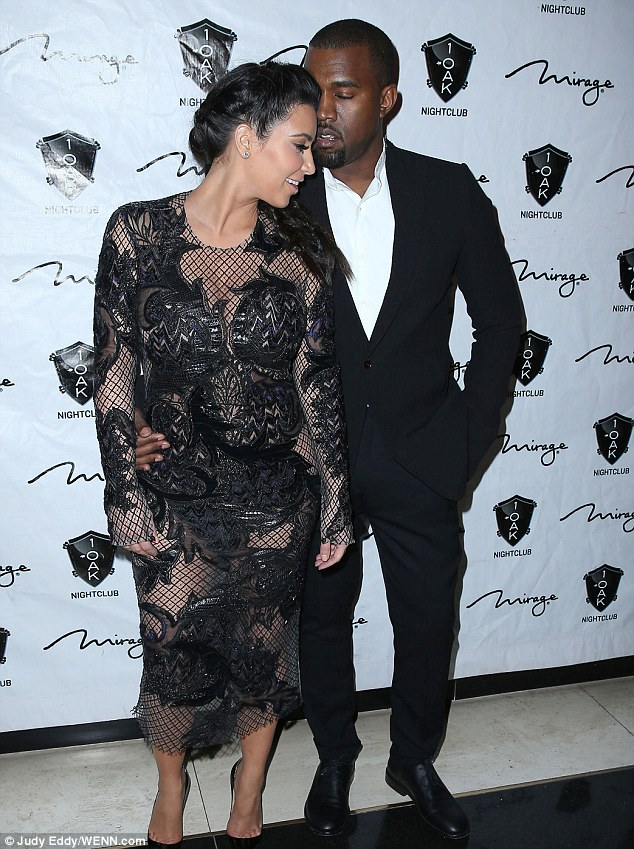 Keeping her close: Kanye puts a protective arm around his pregnant girlfriend as they pose for photos on the red carpet