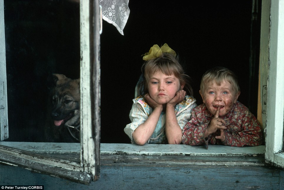Glum: Two dirty children look out the window in a coal-mining and steel-manufacturing community in Siberia enduring widespread economic hardships