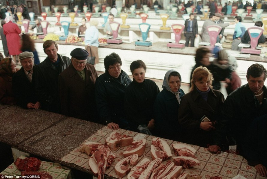 Hindered by centralised market forces: A long queue forms in Novokuznetsk for bacon and other meat from the butcher at a state-run market