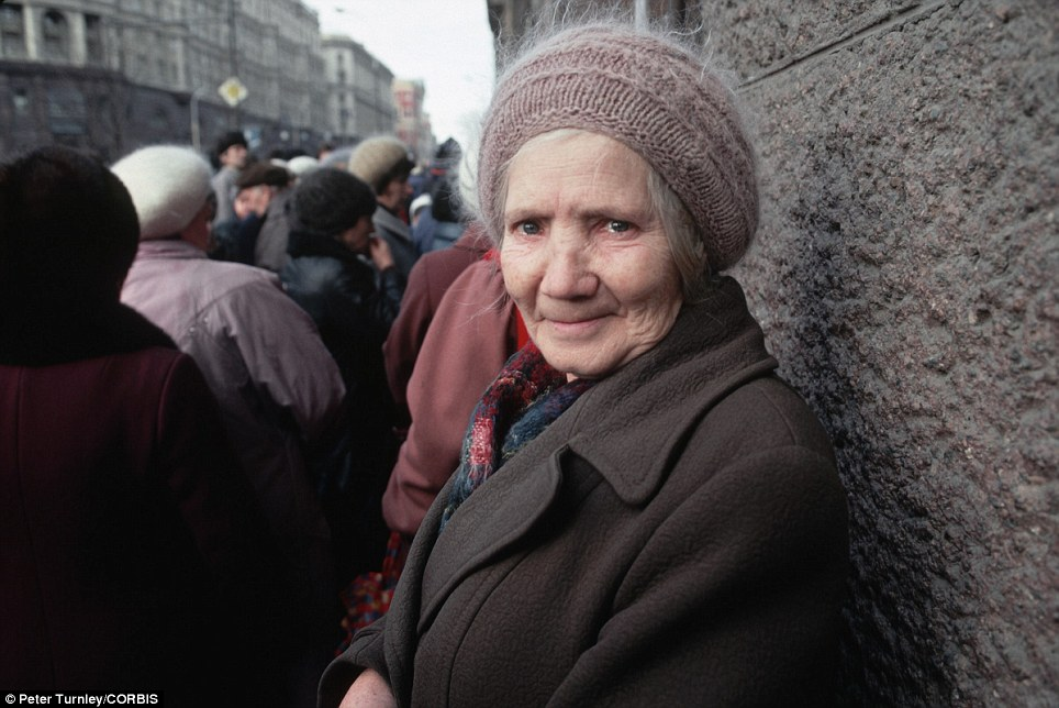 Putting on a brave face: A woman stands near the back of a queue for a market in the Russian capital