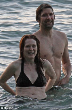 Having a great day: The actress was enjoying a day at the beach with her family and her husband Bart Freundlich was seen cuddling her