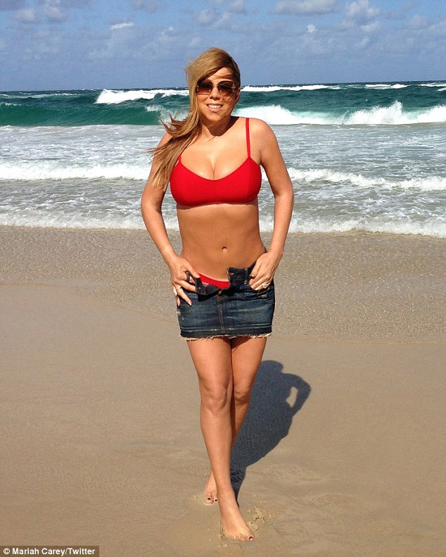 Red hot mum: Mariah Carey flaunted her flat tummy and ample cleavage in a red bikini on an Australian beach this week, but neglected to remove her denim mini-skirt