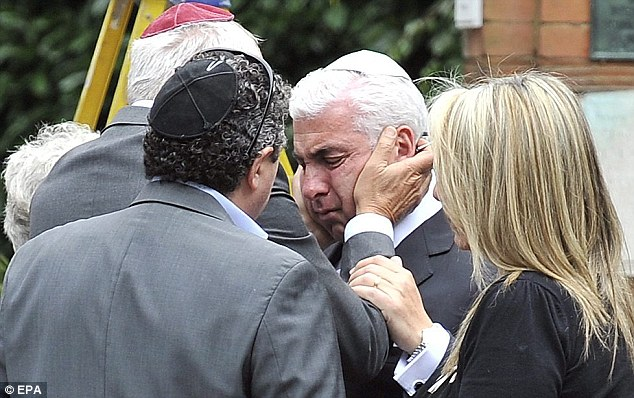 Tragic: Amy's father Mitch is consoled by friends at her funeral in 2011. He said today the family did not want to attend the second inquest