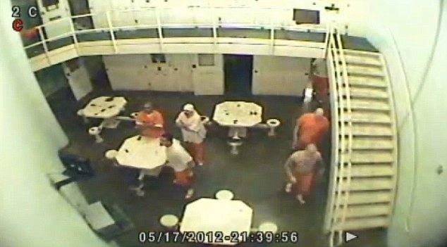 Led to his death: Mollman, bald and dressed in his full prison jumpsuit, seen at right, enters the shot with two others