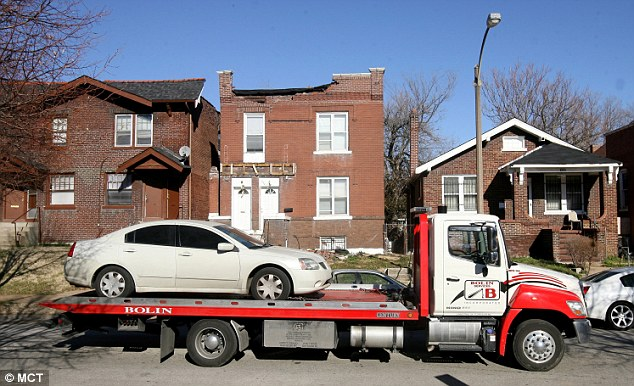 Crime scene: The car was towed on Tuesday to be scoured for evidence by St Louis police