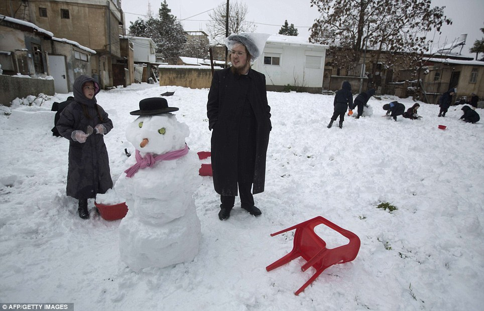 Orthodox Jews enjoy the wintry weather by building snowmen in the Mea Shearim neighborhood of Jerusalem