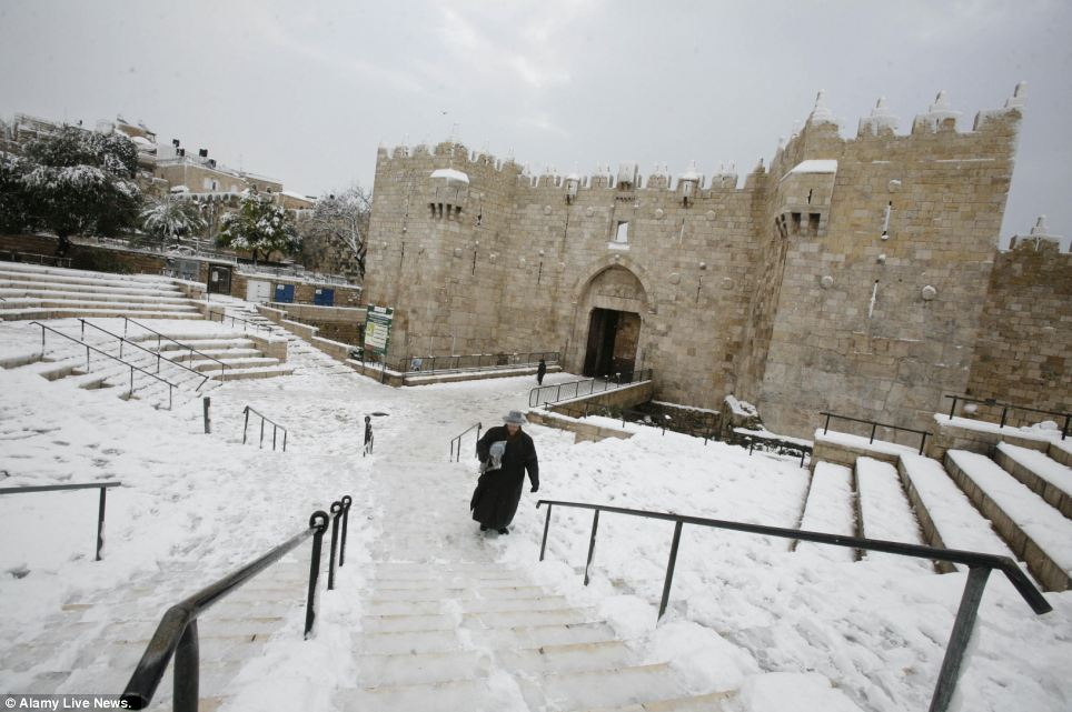 A Jewish man walks as snow falls at the Al-Aqsa mosque compound in the old city of Jerusalem as the city was transformed into a winter wonderland