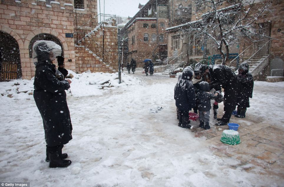 Children huddle round as the snow continues to fall and an older man helps them build a snowman
