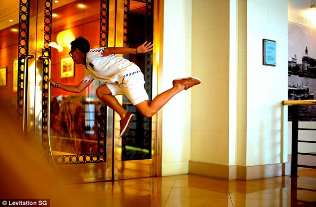 Air time: Another gravity-defying photo as a young man stays suspended in mid-air while opening a door