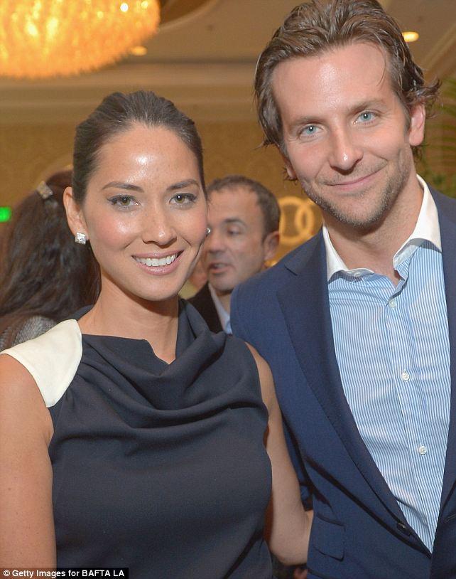 Rubbing shoulders: Olivia posed for a snap alongside a dapper Bradley Cooper