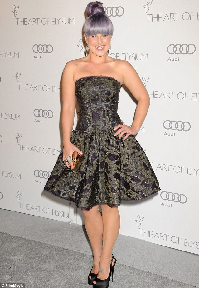 Purple princess: Kelly Osbourne sported an unusual top knot hairdo and a flared purple patterned dress