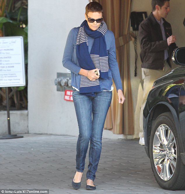 Star in stripes: Charlize went for a more laid back outfit in the afternoon wearing a thick scarf over a blue jumper and jeans