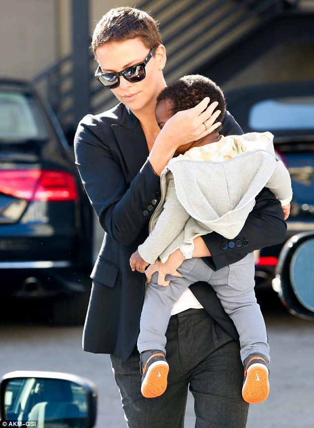 Darling: Charlize Theron cradles her son Jackson out and about in Beverly Hills