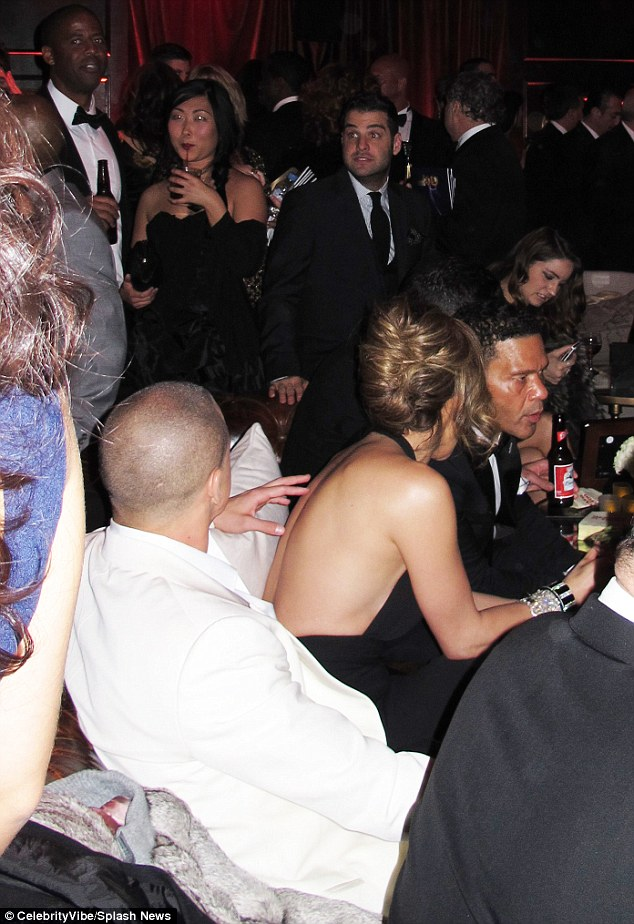 No awkwardness here: Lopez sat down with boyfriend Casper as Diddy mingled in the far distance at the back of the room