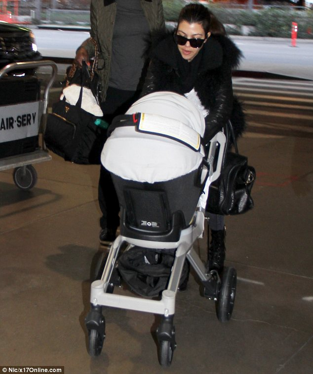 Sister act: Kourtney arrived at the airport a little while after Kim, with her baby Penelope in a stroller