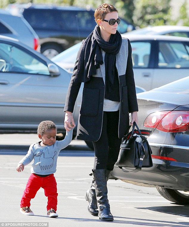 Day out: Theron dressed him in cute red jeans and a grey dragon sweatshirt as they spent time in sunny Beverly Hills