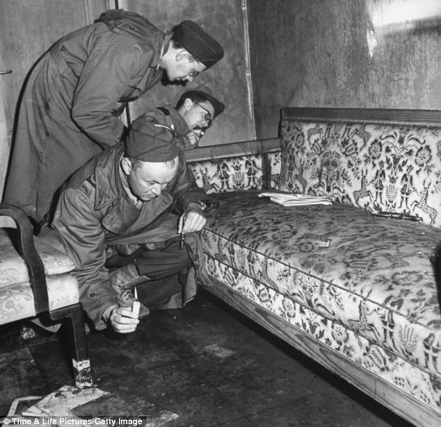 Traces of the dictator: War correspondents examining the arm of sofa stained with blood which might have been Eva Braun's, while one of them uses a candle to search the floor for evidence of suicide in Adolf Hitler's underground shelter